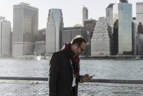 USA, Brooklyn, businessman with smartphone and earphones walking in front of Manhattan skyline — Stock Photo