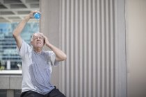 Senior athlete taking break and pouring water over head — Stock Photo