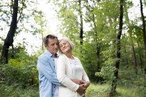 Activo linda pareja senior abrazar juntos en el Parque - foto de stock