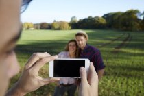 Cell phone picture of couple in countryside — Stock Photo