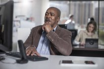 African businessman on computer in city office — Stock Photo