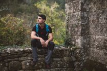 Турист, отдыхающий на каменной стене в природе — стоковое фото