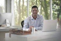 Hombre sentado en el escritorio en la oficina moderna - foto de stock