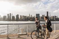Two businessmen with bicycle walking along East River, New York City, USA — Stock Photo