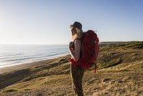 Ragazza adolescente con lo zaino al mare guardando la distanza al crepuscolo della sera — Foto stock