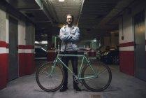 Casual jovem de pé perto de sua bicicleta fixie em uma garagem — Fotografia de Stock