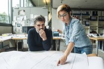 Male and female architects discussing ground plan in office — Stock Photo
