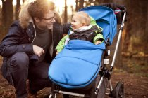 Father smiling at son in buggy in forest — Stock Photo