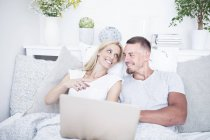 Relaxed couple in bed and using laptop — Stock Photo