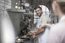 Papá feliz removiendo la olla en la cocina - foto de stock