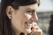 Молода жінка крупним планом з видом на слуховий апарат у вухо на телефон — стокове фото