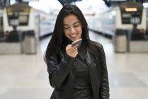 Felice giovane donna con il cellulare alla stazione ferroviaria — Foto stock