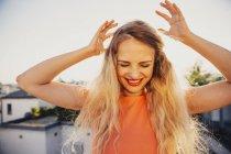Улыбающаяся блондинка танцует на террасе на крыше — стоковое фото