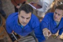 Travailleurs pointant du doigt et regardant vers le haut — Photo de stock