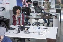 Trabalhador de escritório sorridente sentado na mesa por computador em ambiente de escritório ocupado — Fotografia de Stock