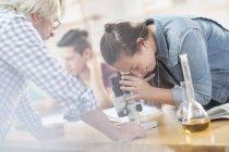 Naturwissenschaftlerin mit Lehrer im Unterricht beim Blick durchs Mikroskop — Stockfoto