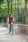 Молодой человек катается на велосипеде по тротуару в городе — стоковое фото