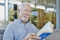 Hombre mayor sentado en la terraza y leyendo libro - foto de stock