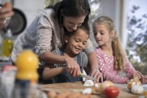 Caucasian cute mother helping daughters in kitchen — Stock Photo