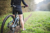 Female mountain biker on trail in forest — Stock Photo