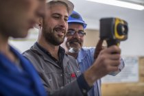 People attending electrician training, students looking at thermal imaging camera — Stock Photo