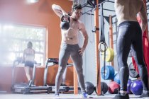 Young man lifting kettlebell in gym — Stock Photo