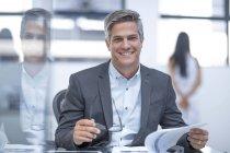 Homme d'affaires de bureau souriant assis au bureau avec ordinateur portable — Photo de stock