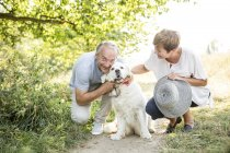 Senior couple with pet dog outdoors in green nature — Stock Photo