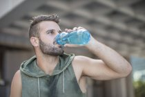 Athlete taking a break in the city drinking water from bottle — Stock Photo