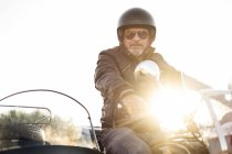 Portrait of cool biker wearing helmet and sunglasses sitting on sidecar motorcycle — Stock Photo