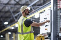 Worker operating machine in industrial factory — Stock Photo