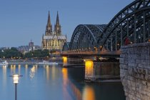 Germany, Cologne, lighted Cologne Cathedral and man sitting on the Hohenzollern Bridge — Stock Photo