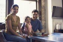 Família feliz sentado na cozinha e olhando para a câmera — Fotografia de Stock