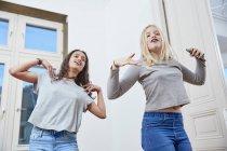 Dos chicas bailando juntas en casa - foto de stock
