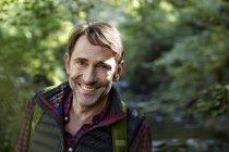 Улыбающийся турист смотрит в камеру в лесу — стоковое фото