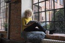 Junge Frau sitzt auf Fensterbank und liest Zeitschrift — Stockfoto