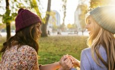 Two best female friends holding hands in park in autumn — Stock Photo