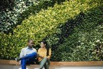 Бизнесмен и женщина сидят перед зеленой стеной завода, используя цифровой планшет — стоковое фото