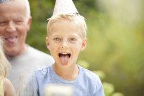Парень в шляпе для вечеринок, высовывает язык — стоковое фото