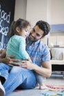 Батько і дочка, сидячи на підлозі з головоломки — стокове фото