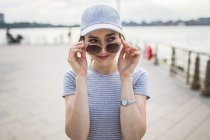 Portrait of woman in baseball cap with sunglasses watching something — Stock Photo
