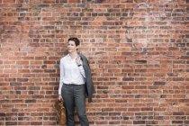 Femme d'affaires debout devant le mur de briques — Photo de stock