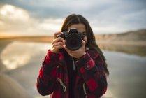 Giovane donna che cattura una foto sulla spiaggia — Foto stock