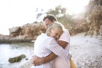 Active cute senior couple hugging together at beach — Stock Photo