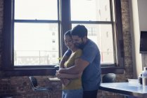 Happy couple cuddling standing at domestic kitchen — Stock Photo