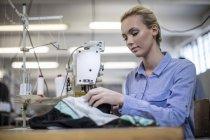 Seamstress working on sewing machine — Stock Photo