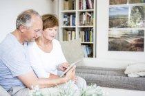 Старшая пара с книгой на диване в гостиной — стоковое фото