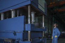 Trabalhador inspecionando máquinas na fábrica — Fotografia de Stock