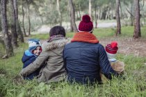 Rear view of family sitting together in forest — Stock Photo