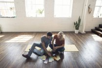 Young couple sitting on carpet in a loft looking at color samples — Stock Photo